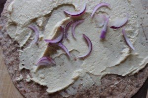 red onion slices on hummus