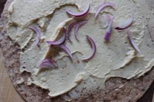 red onion slices on hummus